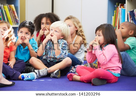 Group of Elementary Pupils In Classroom Touching Noses - stock photo