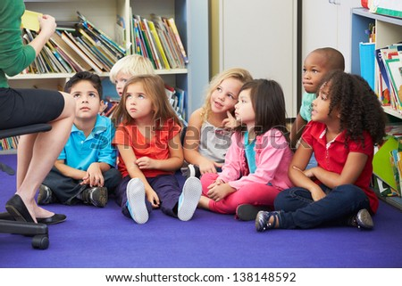 Group of Elementary Pupils In Classroom Working With Teacher - stock photo