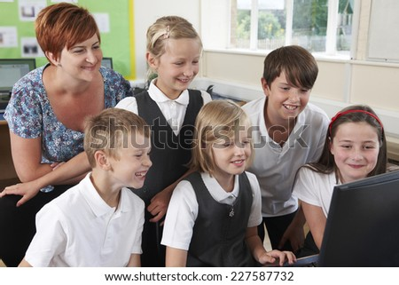 Group Of Elementary Pupils In Computer Class With Teacher - stock photo