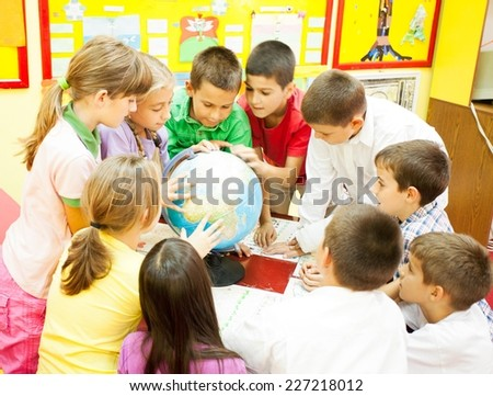 Group of elementary school children sitting around the table in the classroom and looking at the globe.  NOTE: All the drawings and artwork in the classroom are made by children. - stock photo