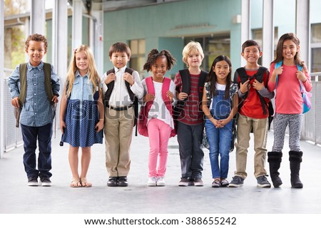 Group of elementary school kids standing in school corridor - stock photo