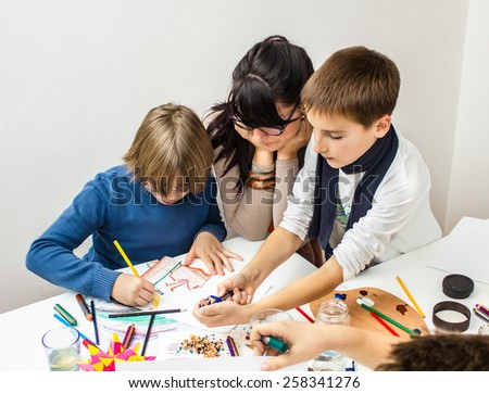 Group of elementary school pupils in classroom - stock photo