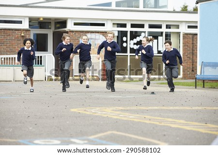 Group Of Elementary School Pupils Running In Playground - stock photo