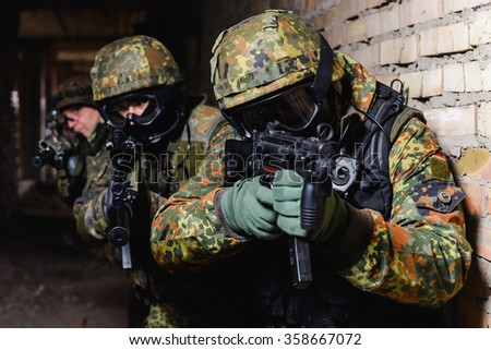 Group of elite police marksmen with weapon in building during a special operation/Team of Special Forces from Germany with weapon