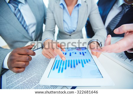 Group of employees discussing financial data in touchpad