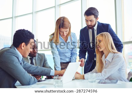 Group of employees discussing ideas and planning work in office - stock photo
