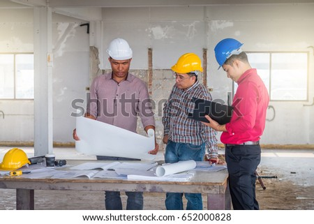 Group engineer checking blueprint on table stock photo 652000828 group of engineer checking the blueprint on the table and talking about construction project with commitment malvernweather Gallery