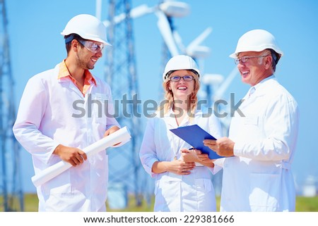 group of engineers on wind power station - stock photo