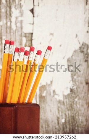 Group of eraser ends of yellow pencils in pencil holder, gray wooden background with copy space, vintage filter effects - stock photo