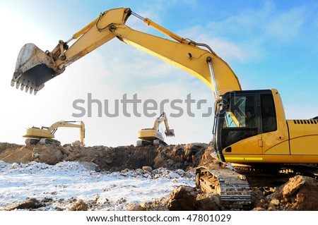 group of excavators loaders at construction site with raised bucket over blue sky in winter - stock photo