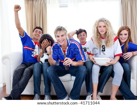 Group of excited and happy teenagers watching a football match in the living-room - stock photo