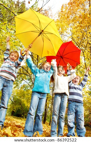 Group of excited kids with red and yellow umbrellas - stock photo