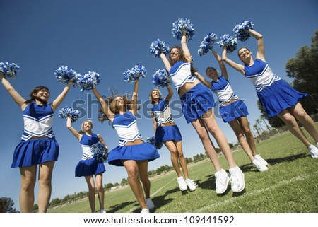 Group of excited young cheerleaders cheering on field - stock photo