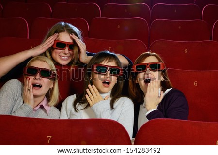 Group of excited young girls watching movie in cinema - stock photo