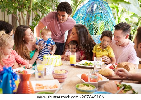 Group Of Families Celebrating Child's Birthday At Home - stock photo
