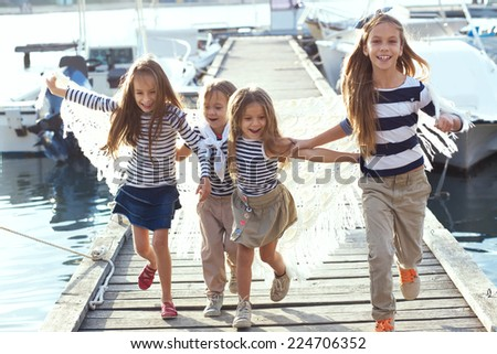 Group of 4 fashion kids wearing same striped navy clothes in marine style running in the sea port - stock photo