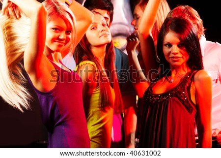 Group of fashionable girls dancing in the night club - stock photo