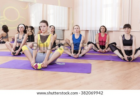 Group of Female Caucasian Sport Athelets Having Indoors Sport Training on Mats. Horizontal Image