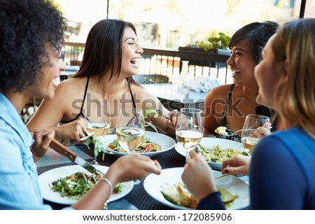 Group Of Female Friends Enjoying Meal At Outdoor Restaurant - stock photo