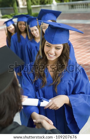 Group of female graduates collecting certificate from female dean - stock photo