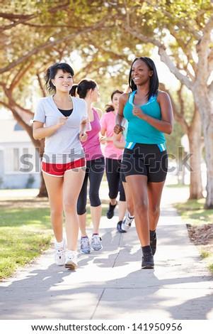 Group Of Female Runners Exercising On Suburban Street - stock photo
