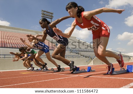 Group of female runners starting the race - stock photo