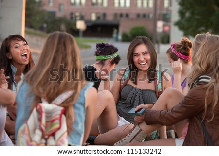 Group of female students sitting outside laughing together - stock photo