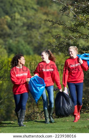 Group Of Female Volunteers Collecting Litter - stock photo