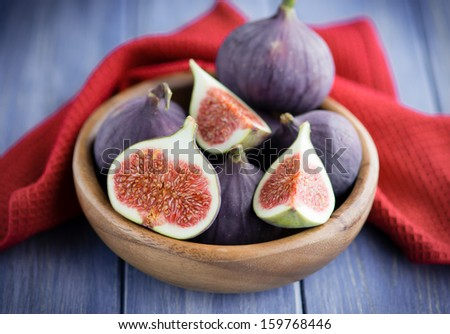 Group of figs in a bowl on rustic blue wooden table with a red towel