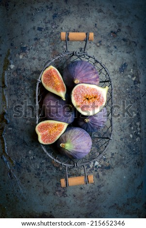 Group of figs in a wire basket  on rustic metal background. Top view still life (blue and purple  toning applied) - stock photo