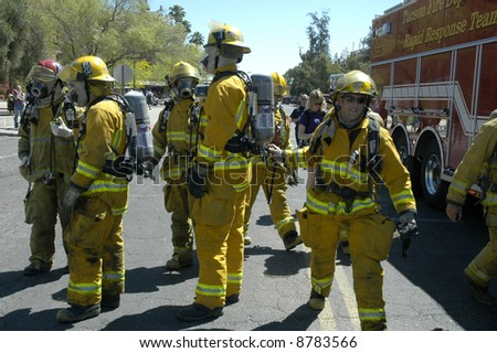 Group of firefighters prepare to respond to an emergency. - stock photo