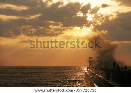 Group of fishermen on the pier near lighthouse with wave splash at sunset, Porto, Portugal