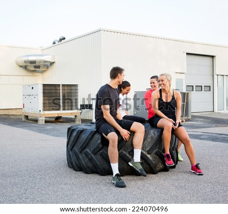 Group of fit friends conversing while relaxing on tire after workout outdoors - stock photo