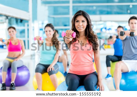 Group of fit people at the gym exercising - stock photo