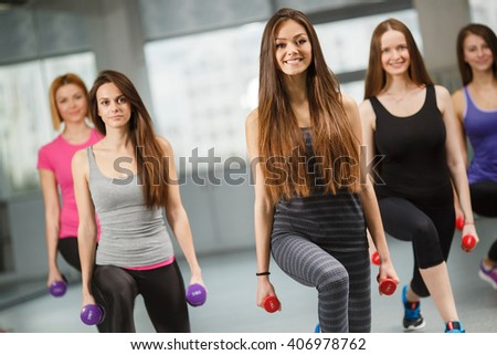 Group of fit people at the gym exercising. Group of people in pilates class doing sportrs on fit balls at gym. group of gym people in an aerobics class - stock photo