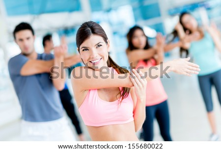 Group of fit people at the gym stretching