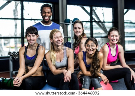 Group of fit people smiling while sitting on exercise balls in the gym - stock photo