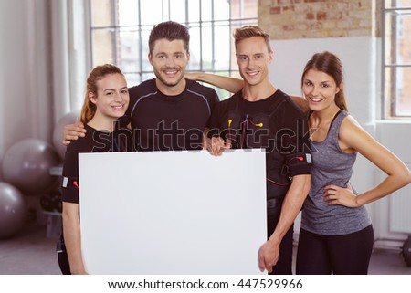 Group of fit young athletes in a ems gym holding a blank white sign in front of them as they stand arm in arm smiling at the camera - stock photo