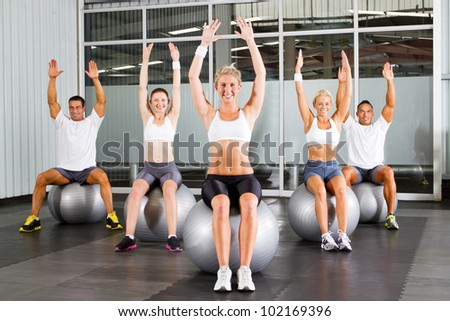 group of fitness people exercise on gymnastic balls in a gym - stock photo