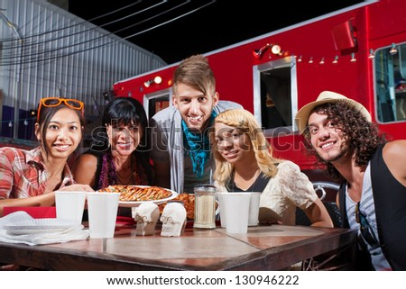 Group of five adults smiling at table near mobile cafe