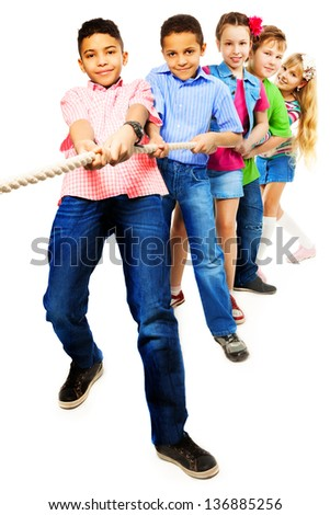 Group of five diversity looking kids, boys and girls pulling the rope together standing in a line as a team, isolated on white with black boy girl on front - stock photo