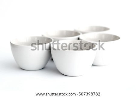 Group of five empty white bowls on white background