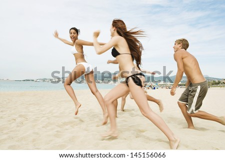 Group of five friends running together towards the sea water shore, being spontaneous and having fun while on a summer vacation on a beach showing happy expressions. - stock photo