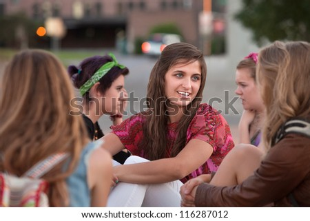Group of five girls talking and sitting together - stock photo