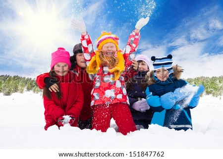 Group of five happy kids, boys and girls throw snow in the air - stock photo