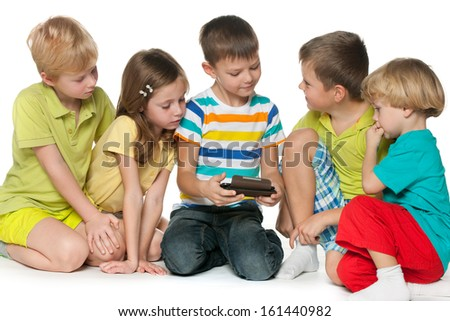 Group of five little children are playing with a new gadget