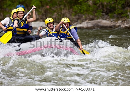 Group of five people whitewater rafting and rowing on river