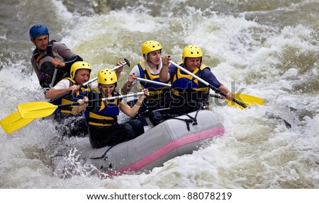 Group of five people whitewater rafting in river - stock photo