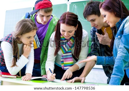 Group of  five  students discussing in classroom - stock photo
