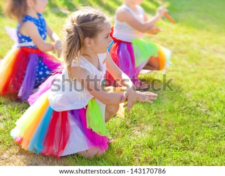 Group of five years old girls dancing during a preschool performance outdoor while a sunny day - stock photo